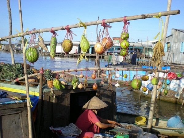 Sellers hang out product samples on a long bamboo in front of the boats