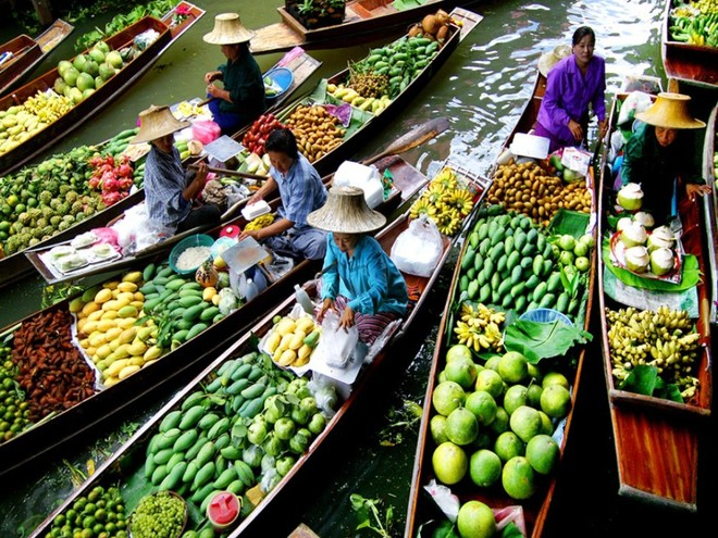 A multitude of boats loaded with many different kinds of tropical fruit by the tone